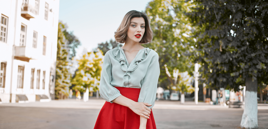 stylish woman in red skirt and blue blouse in the street