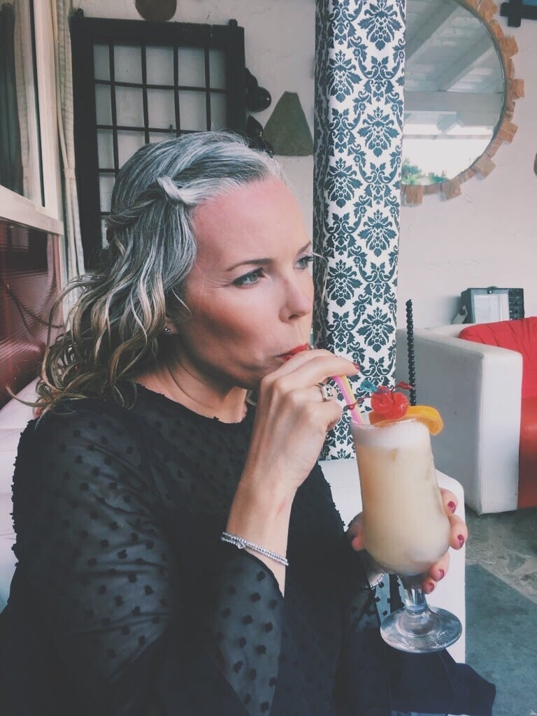 This is what happened when I stopped Dyeing my Hair.  Woman transitioning to grey hair and holding a cocktail.
