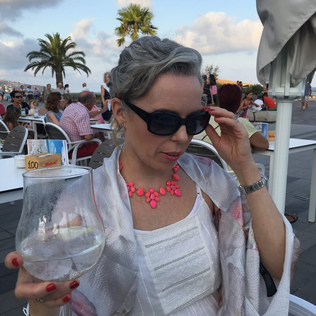 This is what happened when I stopped Dyeing my Hair.  Over 40's woman holding a drink on holiday in Spain.
